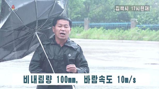"""북한 조선중앙TV는 7일 오후 5시 제10호 태풍 '하이선'의 영향으로 많은 비가 내려 침수된 함경북도 김책시 도로와 건물의 모습을 보도했다. 취재기자는 """"폭우를 동반한 많은 비가 내리면서 도로하수망들이 물이 잘 빠지지 않아 도로에 물이 찼다""""고 전했다. 강풍에 우산이 뒤집힌 채로 중계하는 취재기자의 모습.  /조선중앙TV연합뉴스"""